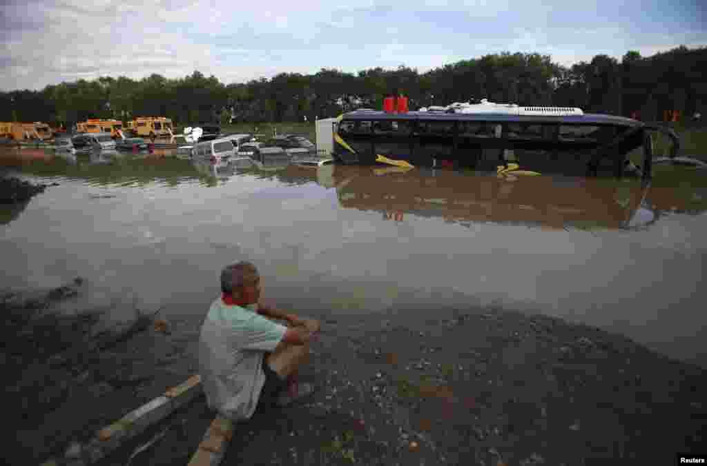 Một người đứng chờ cạnh một xa lộ ngập nước ở quận Phòng Sơn, trong lúc xe của ông bị kẹt dưới trời mưa lớn, 22/7/2012.