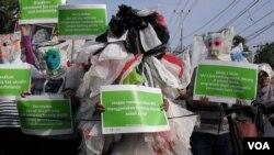 Para aktivis lingkungan Solo membalut seluruh tubuhnya dengan kantong-kantong plastik dalam aksi di sepanjang jalan Slamet Riyadi di Solo, hari Minggu pagi (15/7).