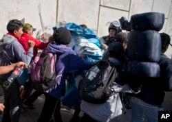 Cientos de migrantes, incluyendo mujeres y niños, convocaron una protesta pacífica en el lado mexicano de la frontera cuando las autoridades mexicanas les ordenaron parar a la espera de un permiso para la manifestación.