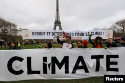 "Environmentalists hold a banner that reads ""Standing and Determined for the Climate"" at a climate conference protest demonstration near the Eiffel Tower in Paris, France, Dec. 12, 2015."