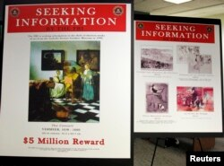 FBI posters displaying works by artists Johannes Vermeer and Edgar Degas are seen during a press conference held to appeal to the public for help in returning artwork stolen in 1990 from the Isabella Stewart Gardner Museum in Boston, Massachusetts.
