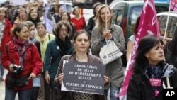 An activist holds a sign as she attends a demonstration a day after the French Constitutional Council decided the immediate repeal of the law on sexual harassment, in Paris, May 5, 2012.