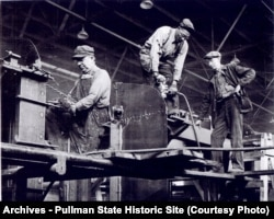 Three riveters working on a Pullman Car ca 1949; black and white men worked together in the factory.