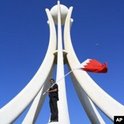 Demonstrator waves Bahraini flag on the Pearl Monument on a main square in Manama, Bahrain, February 15, 2011
