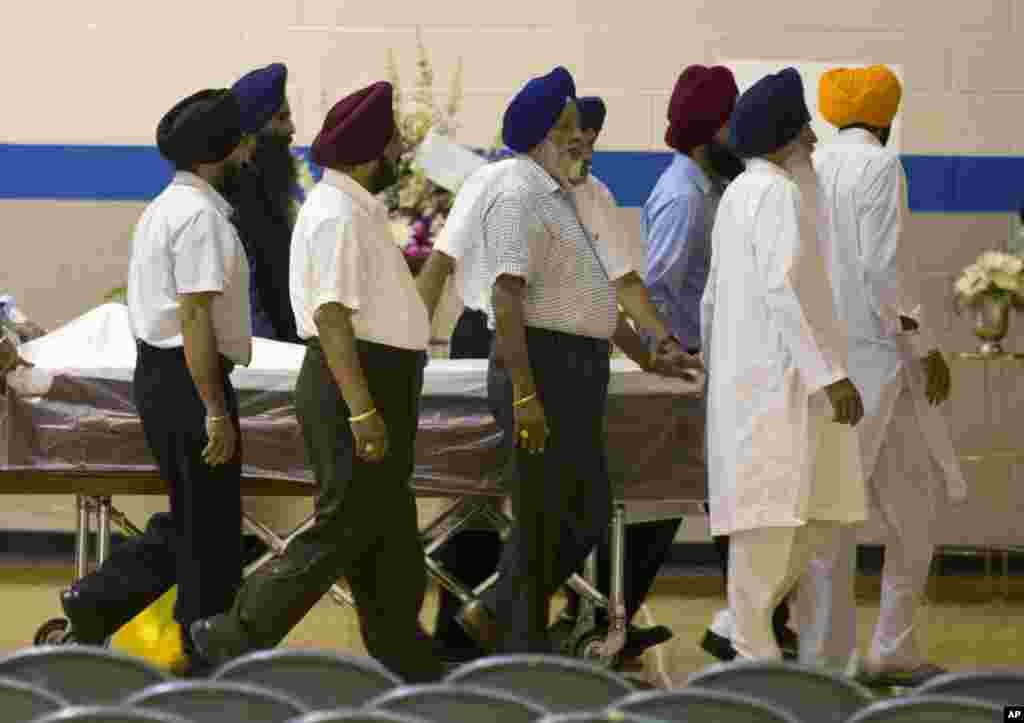 Sikh temple members bring in a casket for the funeral and memorial service for the six victims of the Sikh Temple of Wisconsin mass shooting, August 10, 2012.