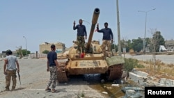 Members of Libya's pro-government forces are seen atop a tank in Benghazi, May 21, 2015.
