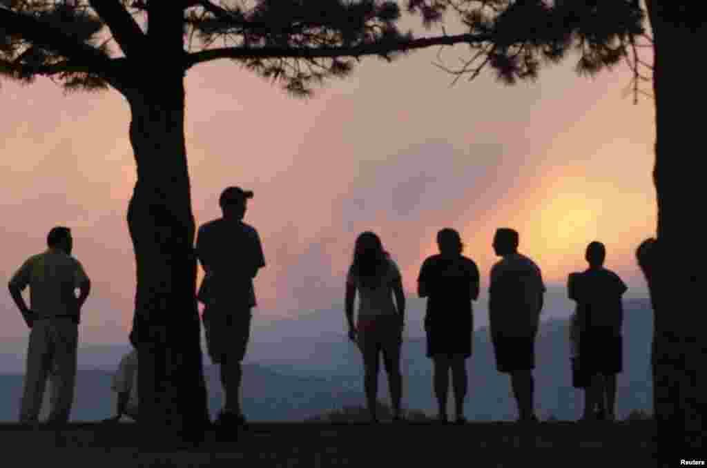 Dân chúng theo dõi một cột khói lớn bốc lên từ Waldo Canyon Fire khi mặt trời lặn, phía tây Colorado Springs.