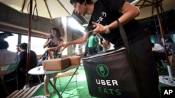 Japan Uber: A delivery man brings ordered food during a press conference of UberEats in Tokyo, Wednesday, Sept. 28, 2016.