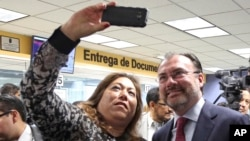 Elisa Jimenez, director of the California Mental Health Connection, takes a selfie with Mexico's Secretary of Foreign Relations Luis Videgaray at the dedication of a mental health facility at the Consulate General of Mexico in Los Angeles, Sept. 12, 2017.