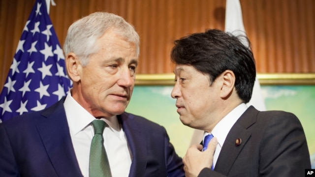 U.S. Defense Secretary Chuck Hagel, left, talks with Japanese Defense Minister Itsunori Onodera, right, as they wait for South Korean Defense Minister Kim Kwan-jin to arrive to begin their meeting, Saturday, May 31, 2014 in Singapore.