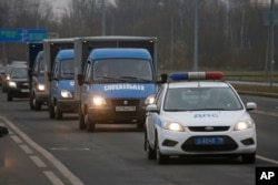 Trucks carry the bodies of the air crash victims from a city morgue to the crematorium for identification in St.Petersburg, Russia, Nov. 2, 2015.