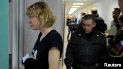 Aktivis Greenpeace Sini Saarela dari Finlandia (kiri) saat memasuki pengadilan di kota Murmansk, Rusia (29/9).