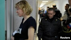 Greenpeace activist Sini Saarela from Finland (L) is escorted at a district court in Murmansk, Russia, Sept. 29, 2013.