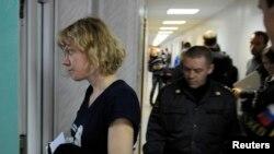 一名绿色和平活动人士被押送进明斯克的一家法庭受审。(2013年9月29日)