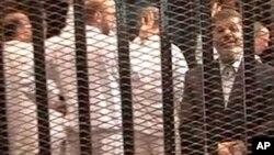 محمد مرسی در کنار دیگر رهبران اخوان المسلمین در قفس، در اولین محاکمه