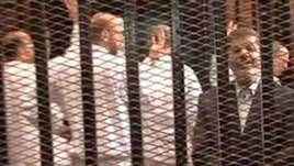FILE - A Nov. 2013 image made from video provided by Egypt's Interior Ministry shows ousted president Mohammed Morsi (R) in a defendant's cage during a trial hearing in Cairo.