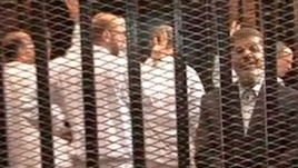 FILE - A Nov. 2013 image made from video provided by Egypt's Interior Ministry shows ousted President Mohammed Morsi (R), speaking from the defendant's cage during a trial hearing in Cairo, Egypt.