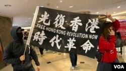 示威者手持標語在尖沙咀海港城商場,進行平安夜和你Sing抗爭行動。(美國之音湯惠芸)