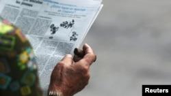 A man smokes a cigar as he reads a local newspaper in Havana, Cuba, Sept. 13, 2016.