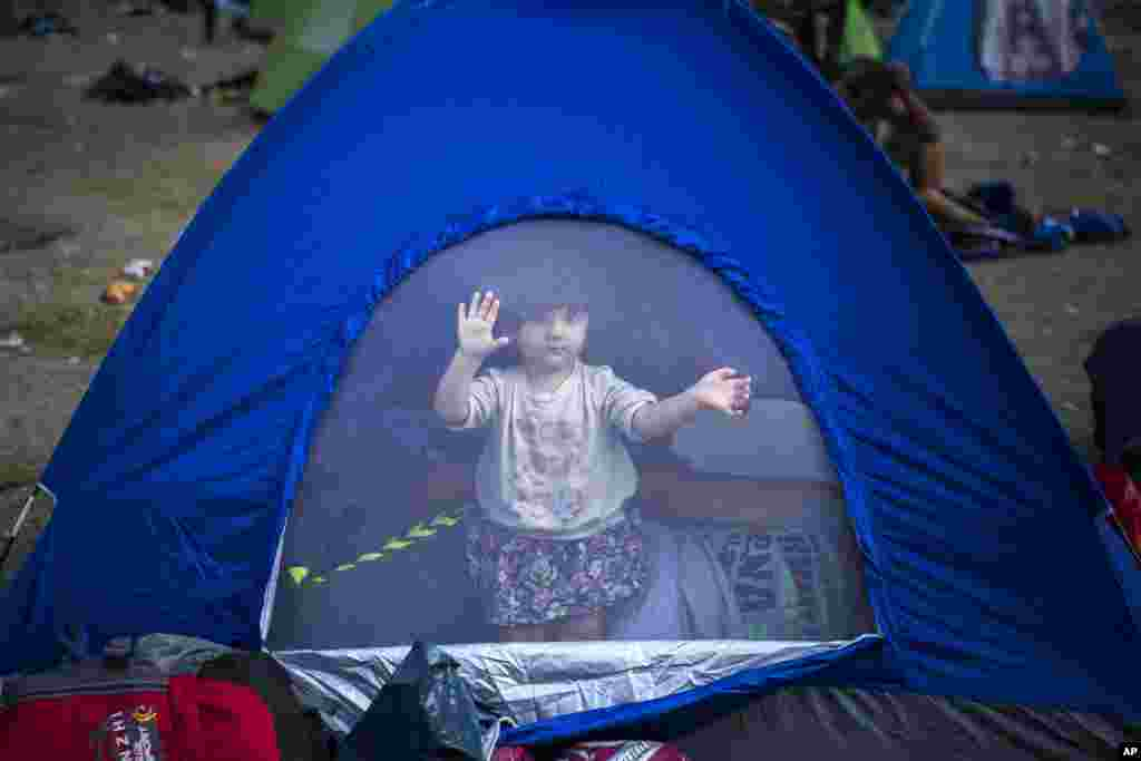A young refugee wakes up inside a tent at a park in Belgrade, Serbia.