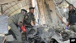 Cảnh sát chống bom mìn đứng trên chiếc xe cài bom bị hư hại hoàn toàn, trong vụ tấn công tại tòa báo This Day