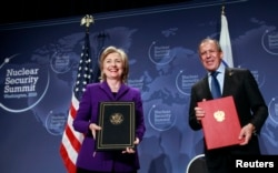 FILE - Then-U.S. Secretary of State Hillary Clinton (L) and Russia's Foreign Minister Sergey Lavrov pose after signing the Plutonium Disposition Protocol during a ceremony at the Washington Convention Center in Washington, Apr. 13, 2010.