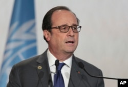 FILE - France's President Francois Hollande speaks during the opening session of the U.N. climate conference in Marrakech, Morocco, Nov. 15, 2016.