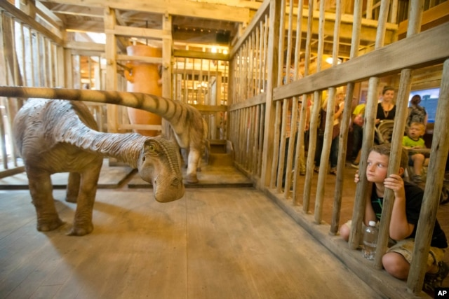 A visitor looks into a cage containing a model dinosaur inside a replica Noah's Ark at the Ark Encounter theme park during a media preview day in Williamstown, Kentucky, July 5, 2016.