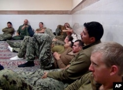 This picture released by the Iranian Revolutionary Guards on Wednesday, Jan. 13, 2016, shows detained American Navy sailors in an undisclosed location in Iran