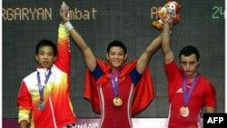 Huy chương vàng Thạch Kim Tuấn, Việt Nam (giữa), huy chương bạc Xie Jiawu, Trung Quốc (trái), và huy chương đồng Smbat Margaryan, Armenia tại lễ trao huy chương môn cử tạ nam, hạng cân 56kg ở trung tâm thể thao Toa Payoh, Olympic Trẻ Singapore 2010, ngày