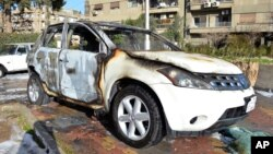 This photo released by the Syrian official news agency SANA, shows cars that were burned after rebels fired rockets and mortar shells that struck several areas in the capital Damascus, Syria, Feb. 5, 2015.