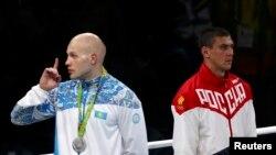 Petinju peraih medali perak Vassiliy Levit dari Kazakhstan (kiri) meminta penonton diam sementara peraih medali emas Evgeny Tishchenko dari Rusia berdiri di sebelahnya saat lagu kebangsaan dikumandangkan di Olimpiade Rio de Janeiro (15/8). (Reuters/Yves Herman)