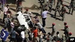 Protesters and military police tussle over trying to overturn a police car after protesters broke the windows in front of the court complex in Suez, Egypt, July 6, 2011