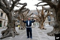 FILE - Chinese artist Ai Weiwei poses for photographers with one of his pieces at his exhibition at the Royal Academy of Arts in London, Sept. 15, 2015.