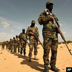 Members of Somalia's al-Shabaab militant group parade during a demonstration to announce integration with al Qaida, in Elasha, south of the capital Mogadishu, February 13, 2012