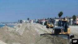 Un tractor apila arena para proteger la playa de la marea que se espera provoque la tormenta Norbert en California.