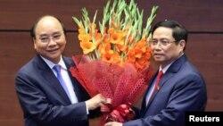 លោក Nguyen Xuan Phuc (ឆ្វេង) ដែលបានក្លាយជាប្រធានាធិបតីថ្មីនៅក្នុងពិធីផ្លូវការមួយនៅទីក្រុងហាណូយនៃប្រទេសវៀតណាម នៅថ្ងៃទី៥ ខែមេសា ឆ្នាំ២០២១ កាន់បាច់ផ្កាជាមួយលោក Pham Minh Chinh នាយករដ្ឋមន្រ្តីថ្មី របស់ប្រទេសវៀតណាម។