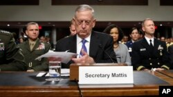 Defense Secretary Jim Mattis, center, prepares to testify on Capitol Hill in Washington, June 13, 2017, before a Senate Armed Services Committee hearing.