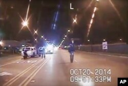 FILE - A frame grab from dash-cam video provided by the Chicago Police Department shows Laquan McDonald (R) walks down the street moments before being shot by officer Jason Van Dyke on Oct. 20, 2015.