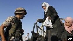 Un soldado jordano ayuda a refugiados sirios que cruzan la frontera.
