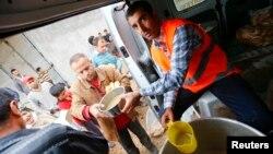 16일 터키 수루크의 난민캠프에서 터키 구호요원들이 시리아 코바니 출신 난민들에게 식량을 나눠주고 있다.