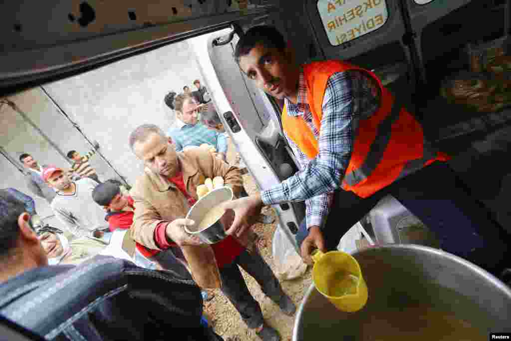 A Turkish aid worker distributes food to refugees from Kobani, Syria now living in a refugee camp in Suruc, Turkey, Oct. 16, 2014.