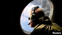 FILE - A crew member looks out an observation window aboard a Royal New Zealand Air Force (RNZAF) P3 Orion maritime search aircraft as it flies over the southern Indian Ocean looking for debris from missing Malaysian Airlines flight MH370.