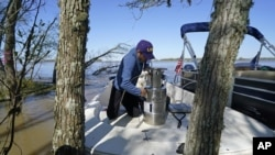 Andre Rabay, research scientist for the LSU Department of Oceanography and Coastal Science, prepares a canister of liquid nitrogen that he will use to freeze samples of the ground on Mike Island, part of the Wax Lake Delta in the Atchafalaya Basin, in St.