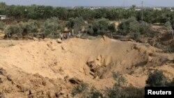 加沙地帶中部的巴勒斯坦男孩看著一處彈坑。警方說,彈坑是以色列空襲造成的。(2014年7月7日)