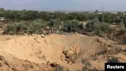 加沙地带中部的巴勒斯坦男孩看着一处弹坑。警方说,弹坑是以色列空袭造成的。(2014年7月7日)