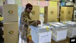Seorang perempuan memasukkan surat suaranya ke dalam kotak suara di salah satu TPS di Mbare, Harare, Zimbabwe (31/7).
