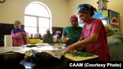 FILE - Members of the Sikh Temple in Oak Creek, Wisconsin, prepare a communal meal for the community.