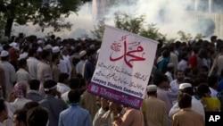 Warga Pakistan yang berujuk rasa berdiri di dekat kontainer yang memblokir jalanan menuju Kedubes AS di Islamabad, Pakistan (21/9). Pihak berwenang Pakistan telah memblokir layanan telepon genggam di 15 kota di Pakistan, termasuk di ibukota Islamabad.