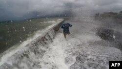 Ombak menerjang tembok pembatas di Legaspi, provinsi Albay, Filipina ketika badai Melor mendekati wilayah ini Senin (14/12).